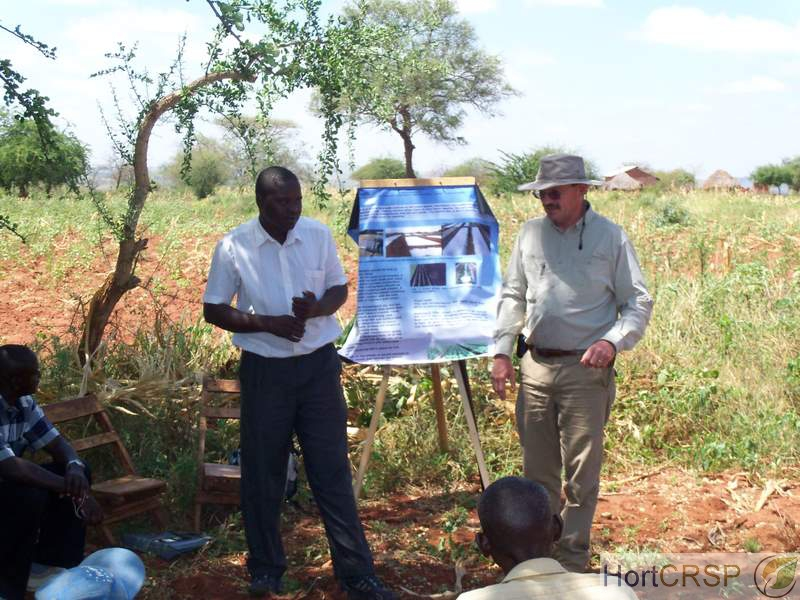 American and Kenyan men lead a farming extension class with poster, outside in Kenya