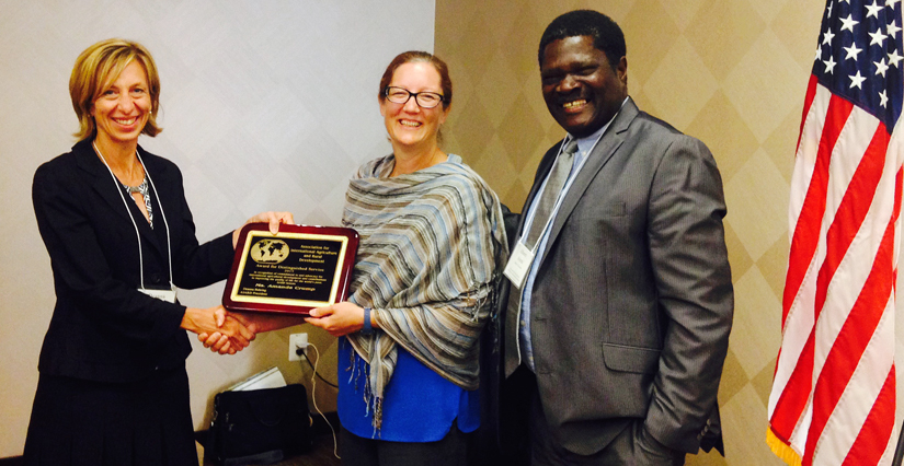 Two women shake hands, holding a plaque, man stands next to them, all smiling