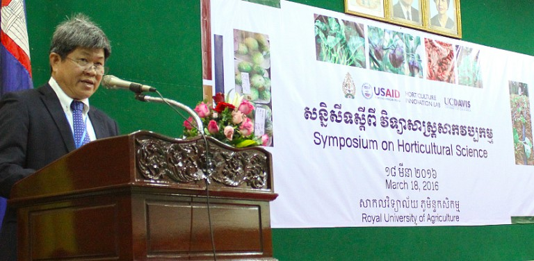"Bunthan speaks at podium, in front of a poster that reads ""Symposium on Horticultural Science"""