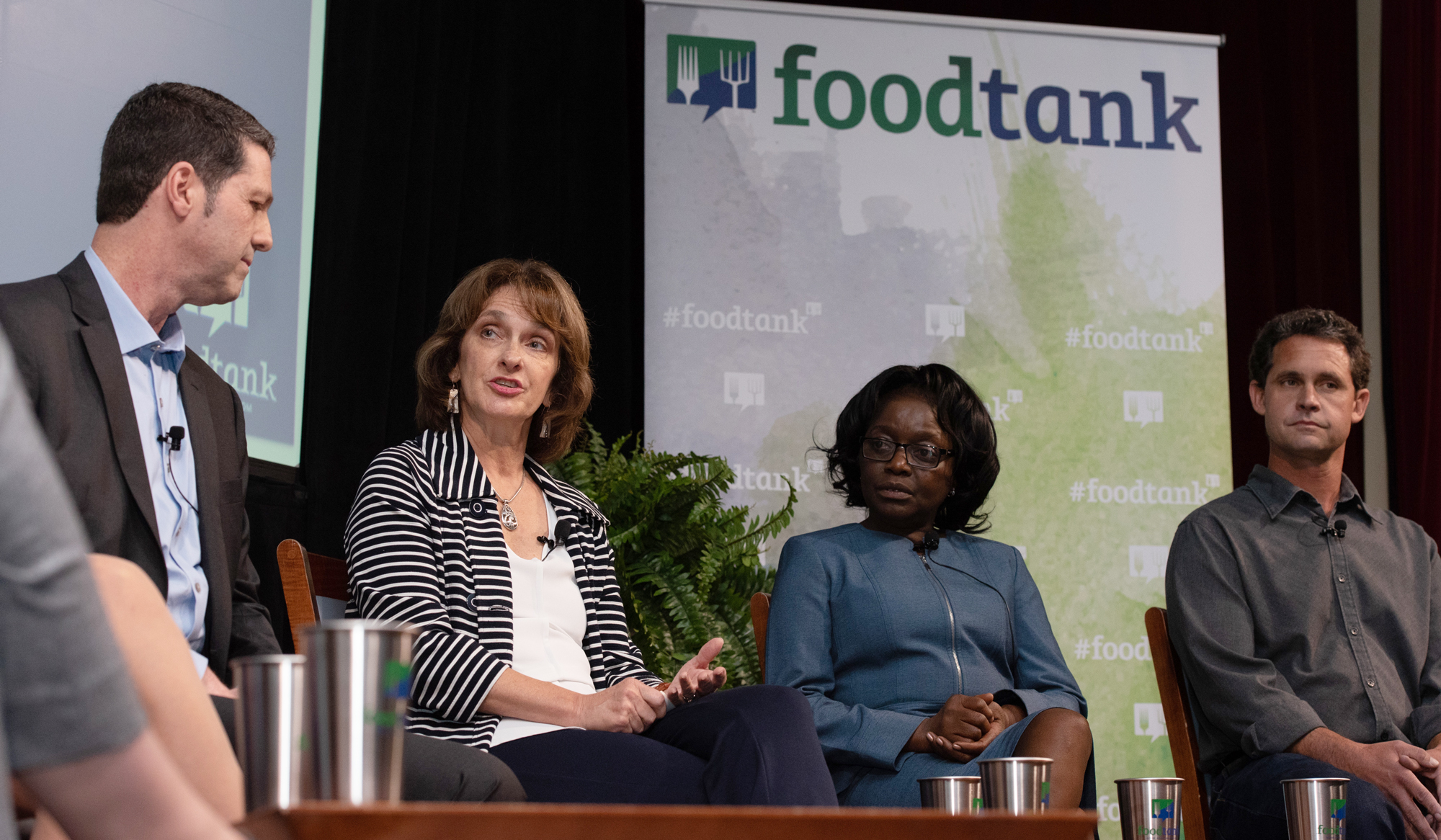 "Beth Mitcham speaking on conference stage, next to Jane Ambuko, with two panelists listening, ""foodtank"" visible in background banner"