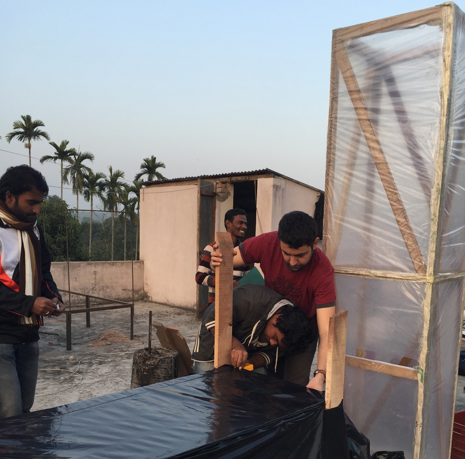 Two researchers connect a black table to a clear chimney to build a solar dryer