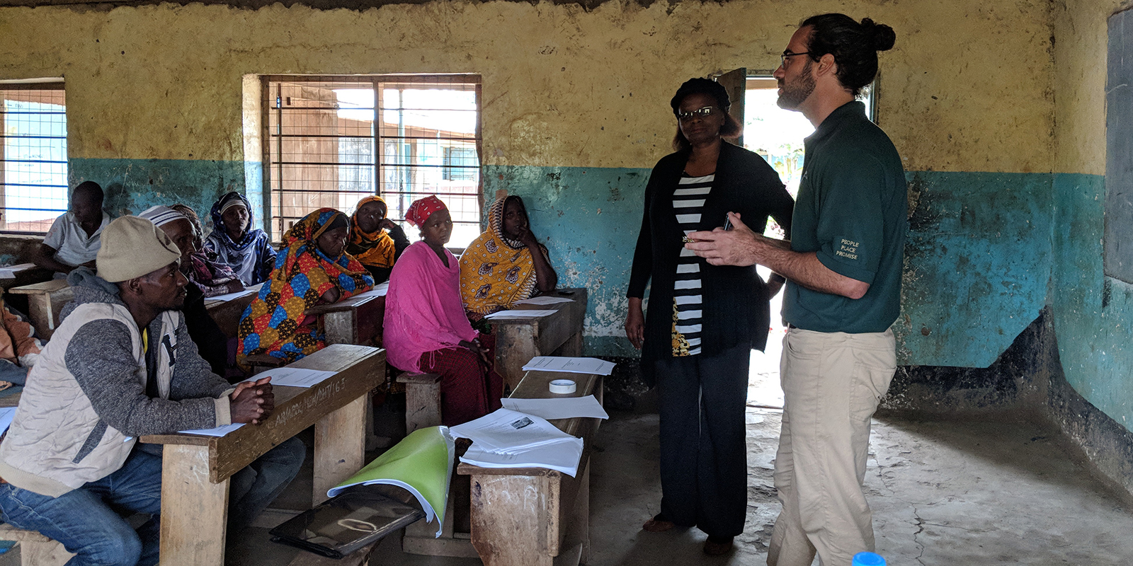 UH Manoa student with local extension agent at front of classroom full of farmers and agricultural professionals in Tanzania