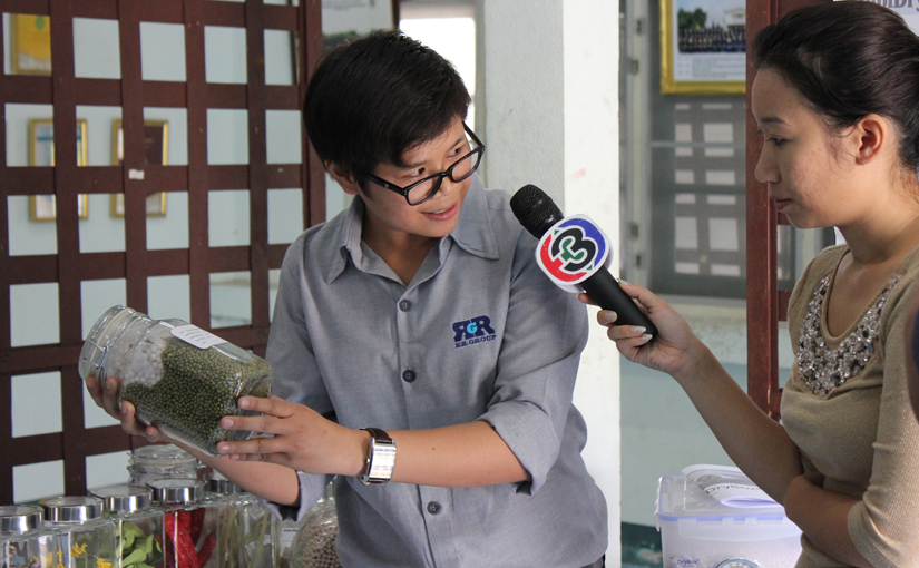 Woman holds jar of drying beads and seeds, speaking into TV microphone held by a reporter