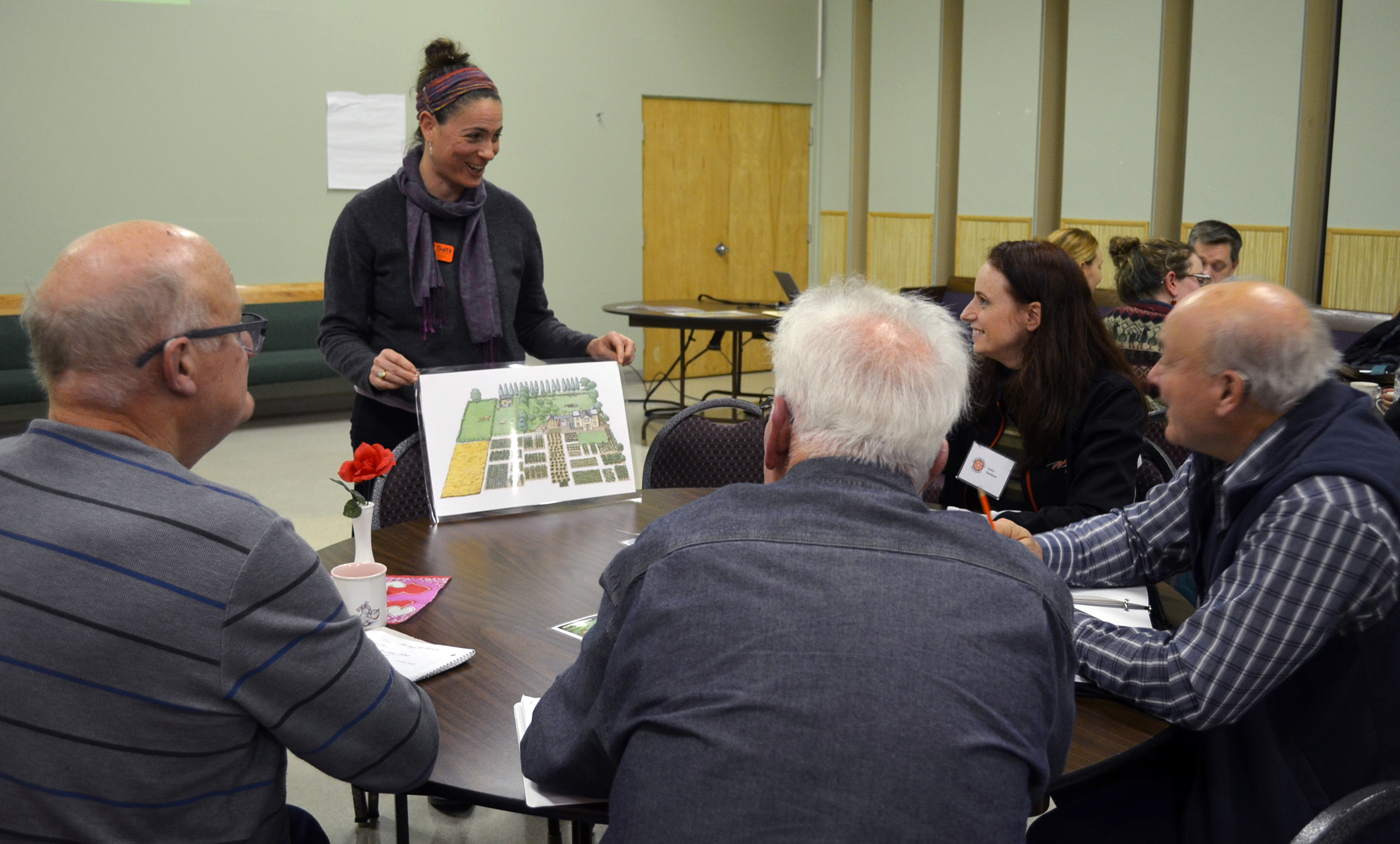 Woman leads discussion about a garden map with a group of community members at an educational event