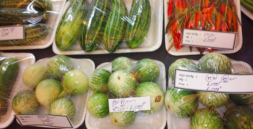 Fresh vegetables sit on Styrofoam trays covered in cling wrap with labels