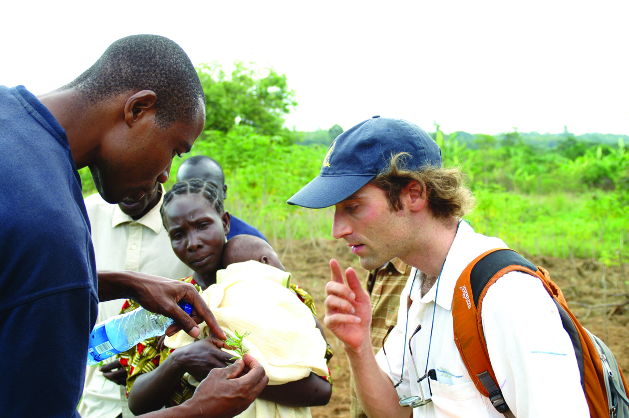 staff member shows student plant detail with farmer in background, in kenya