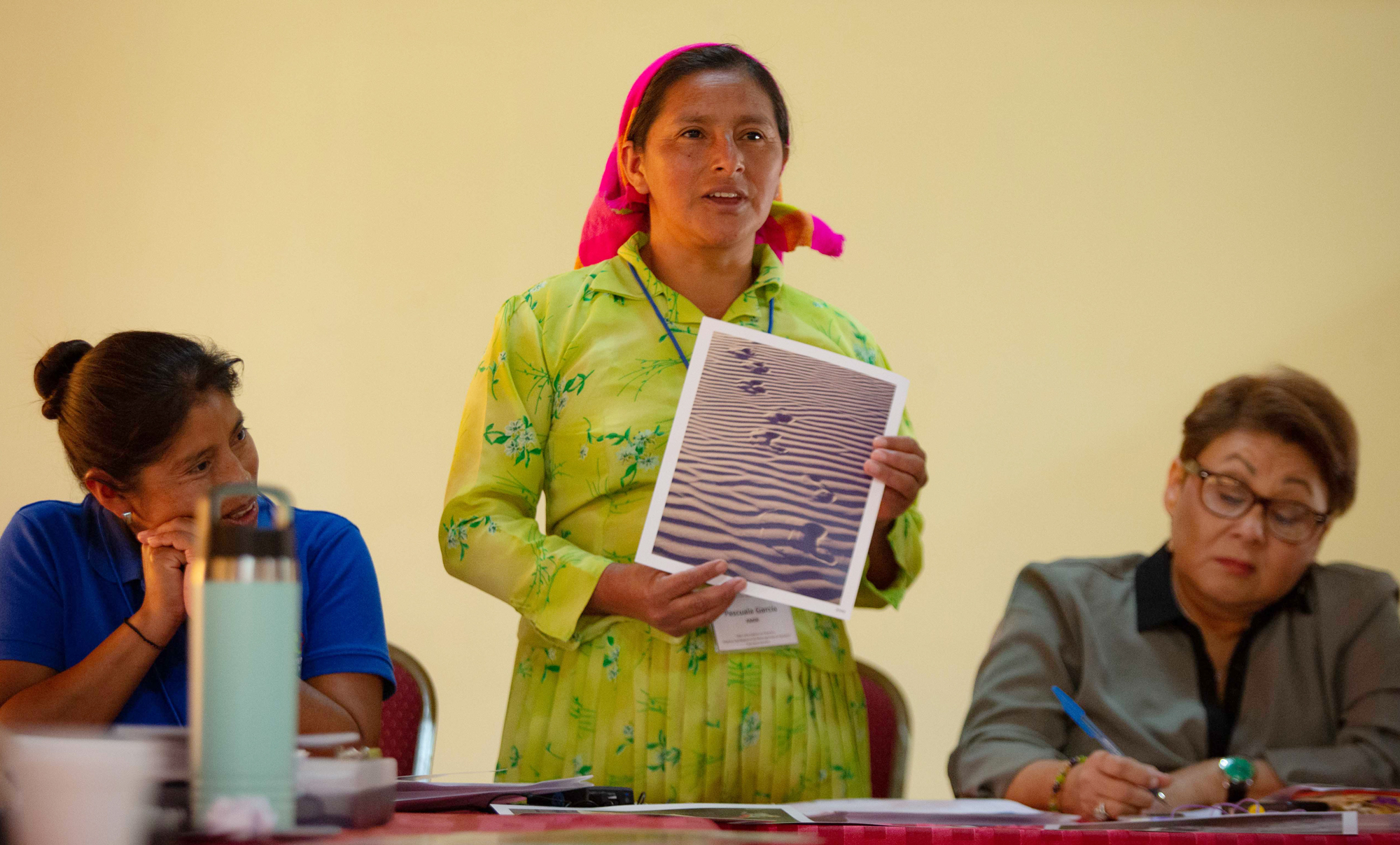 Woman in traditional dress stands at a meeting to speak, holding a photo, with professional women seated on either side of her