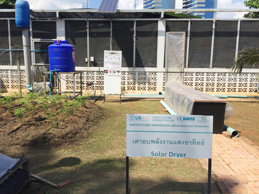 "Sign with Thai words and ""solar dryer"" with chimney solar dryer and water tank in background"