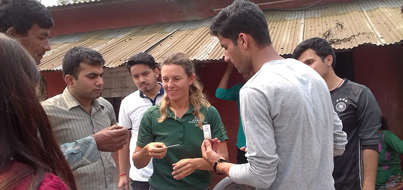 Grad student woman looking at paper test indicator offered by a Nepalese man, with group looking on at farm