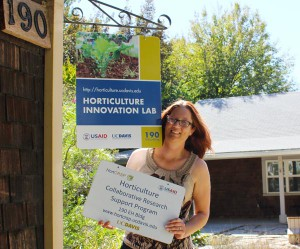 Amanda Crump, associate director, hangs a new office sign as the program adjusts to its new name, the Horticulture Innovation Lab