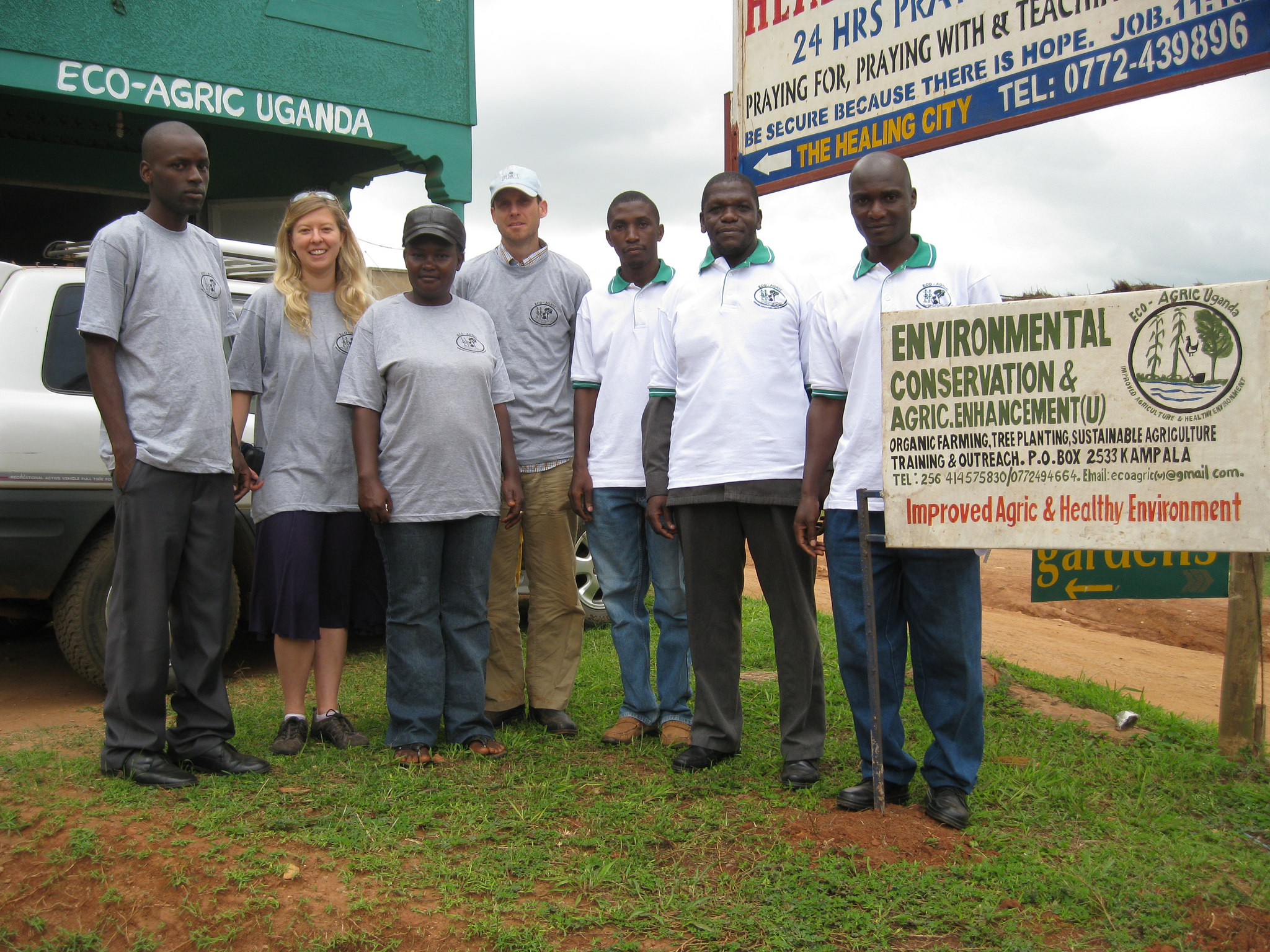 "Group of Ugandan staff and volunteers, Shapland, and Peach-Fine in matching shirts stand next to a sign that reads ""environmental conservation & agric.enhancement (U)...improved agric & healthy environment"""