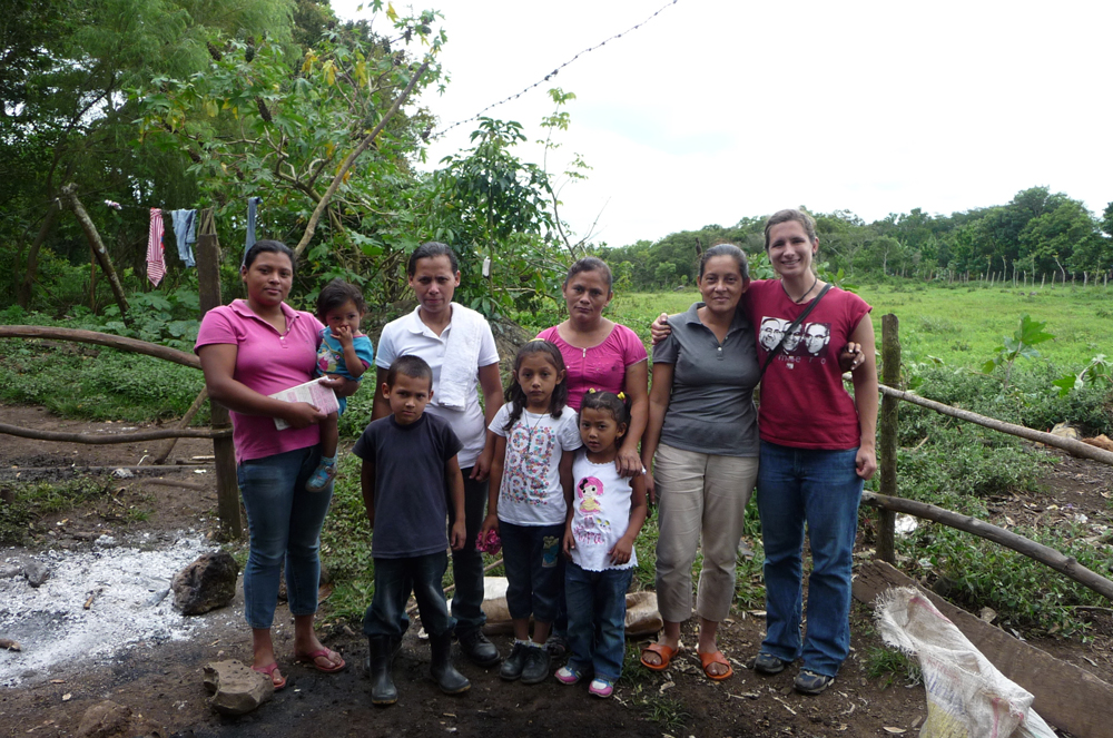 Angel Cruz poses in a plot with farmers and their family