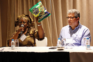 Woman sitting behind table with microphone holds up a bag, man sits next to her