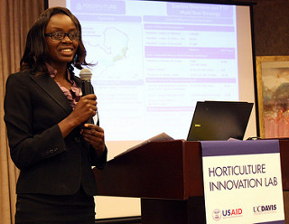 "Woman stands at podium with microphone in front of a screen, podium reads ""Horticulture Innovation Lab"""