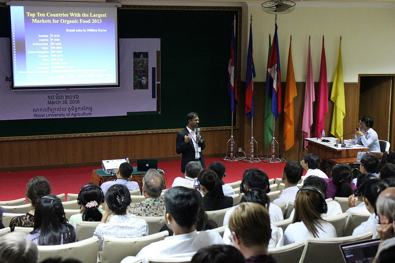 "Govindasamy stands in front of a seated crowd, holding a microphone, in a lecture hall. Screen reads ""top ten countries with the largest markets for organic food 2013,"" seven flags in the right of the room"
