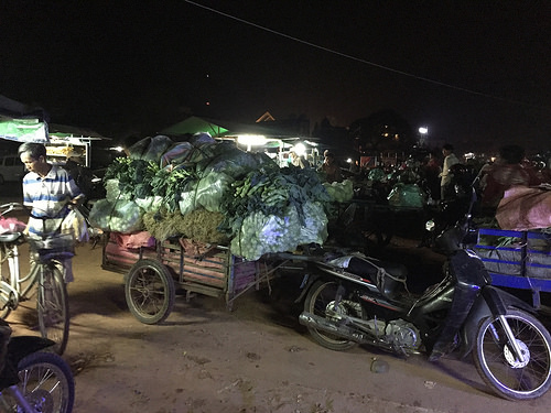 A wagon pulled by motorbike is piled high with bags of vegetables