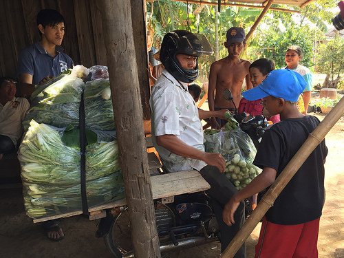 A man prepared to pull out astride a motorbike piled with bagged vegetables