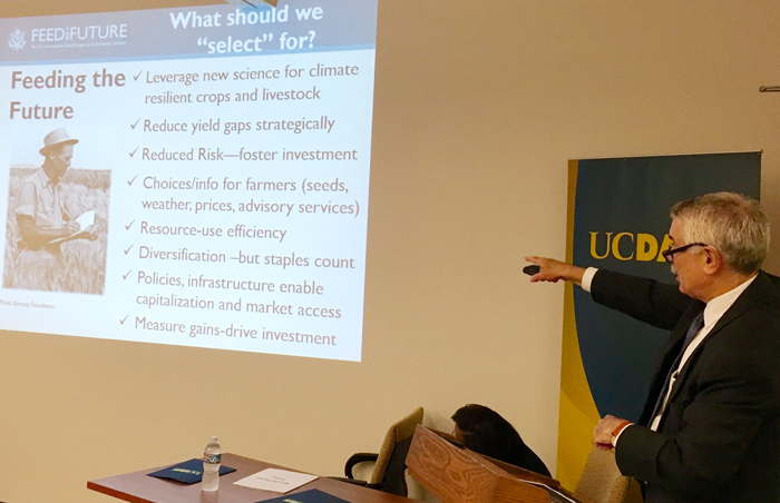Bertram pointing at Feed the Future powerpoint slide with UC Davis banner in background
