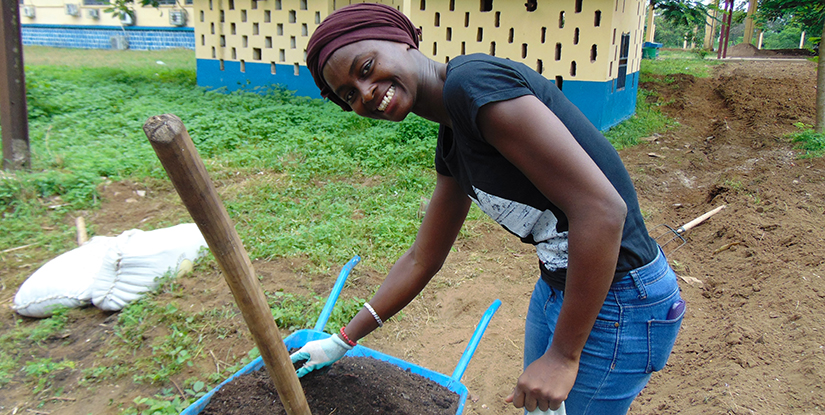 young woman digging with wheelbarrow
