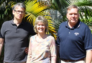 Group photo, three people in front of palms