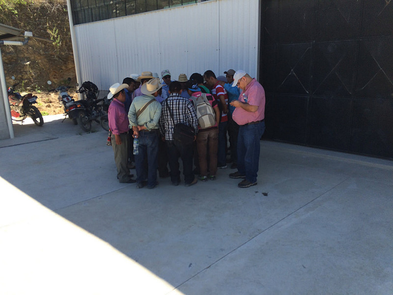 Group huddles together, outside in the shade of a building