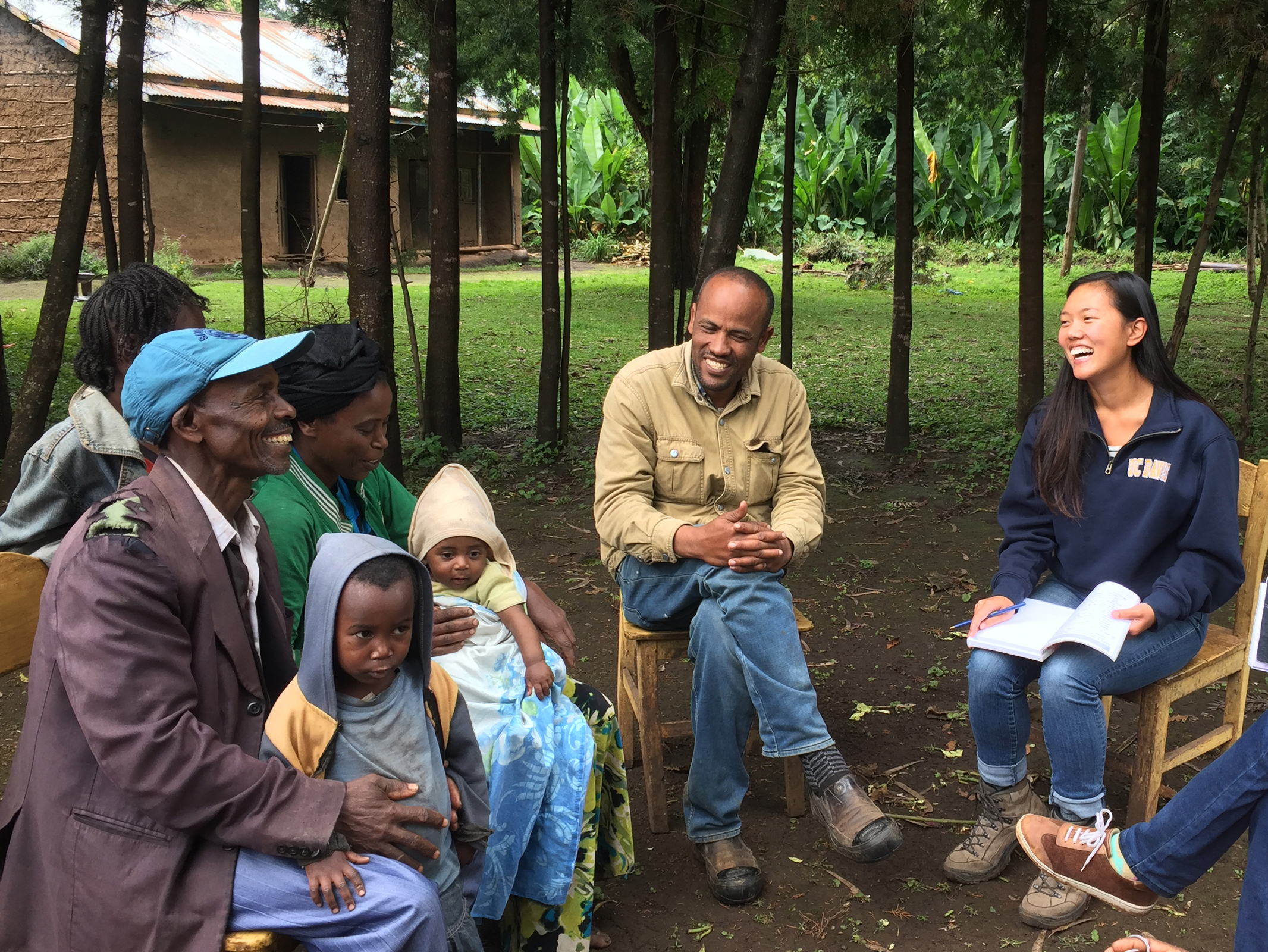 Seated outside in Ethiopia, group of farmers discusses sweet potato crop with local researchers and a UC Davis student