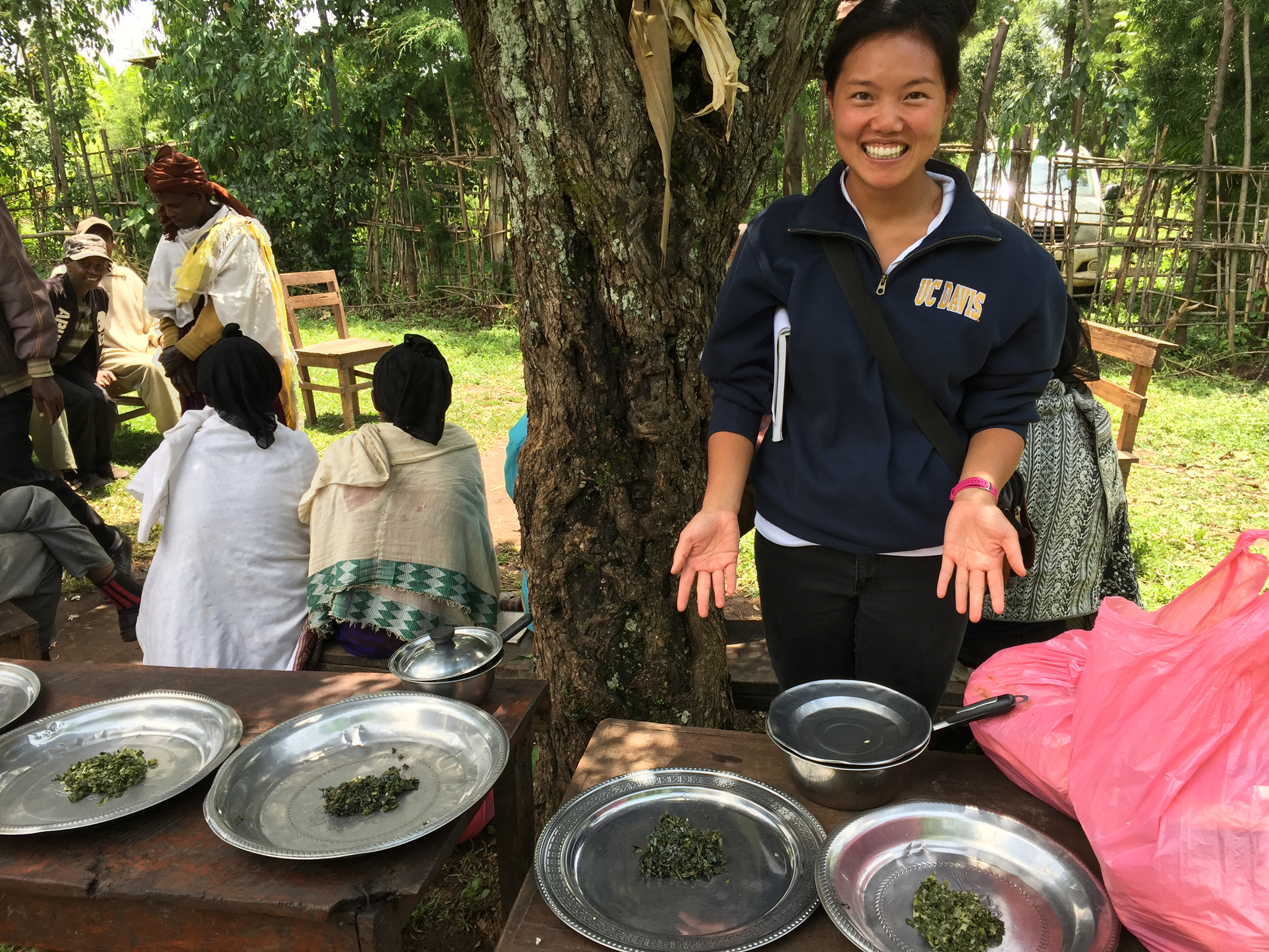 UC Davis student gestures to plates of cooked leafy greens, outside with farmers in Ethiopia