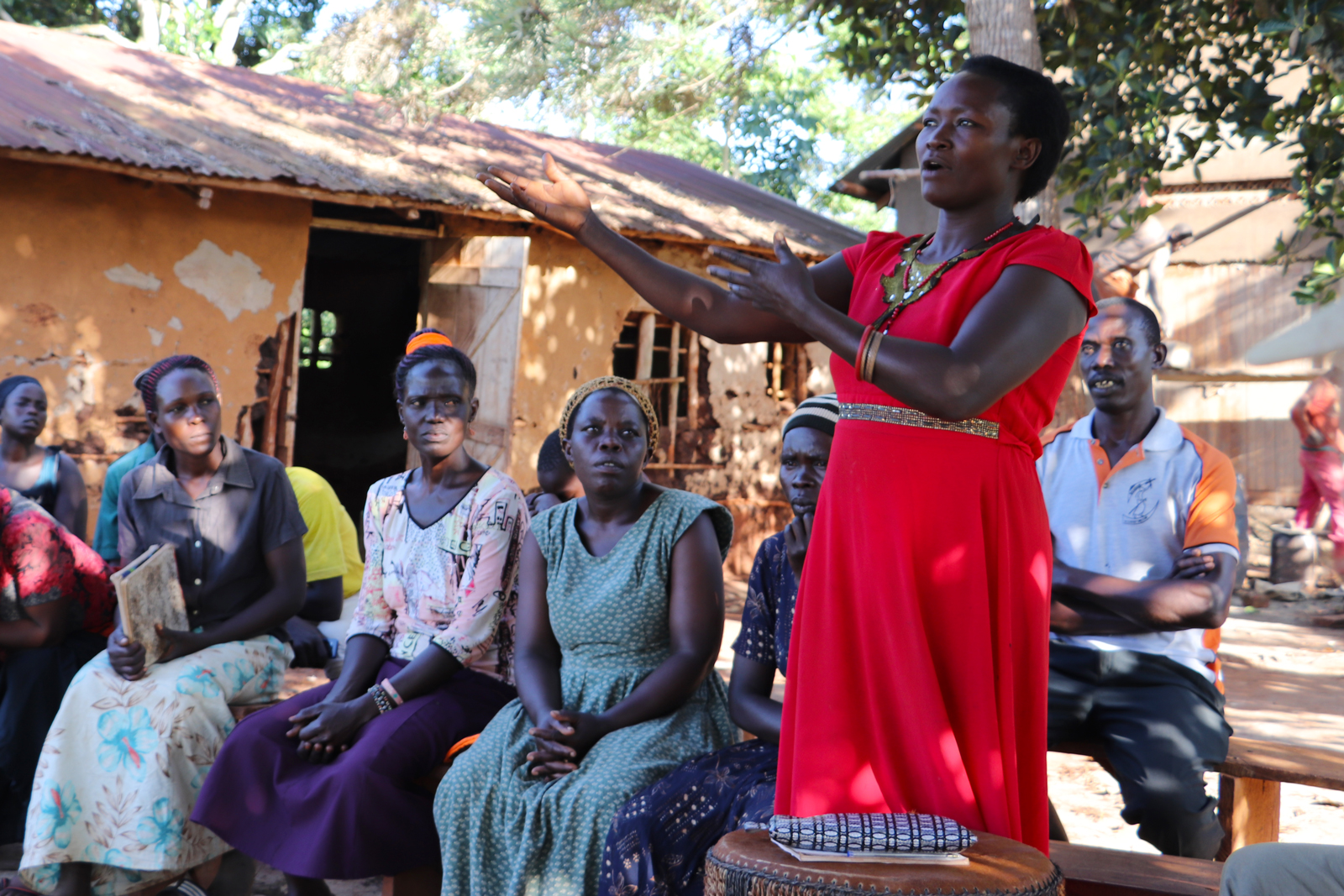 At an outdoor meeting of farmers in Uganda, a woman stands and speaks to the group