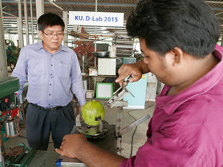 "In front of a sign that reads ""D-Lab"", man uses machine to open a coconut, other man looks on"