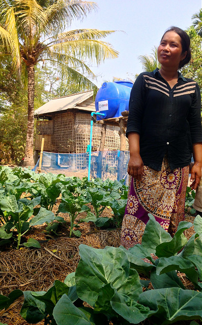 woman farmer stands in field among leafy vegetables and mulch, with water tank in background