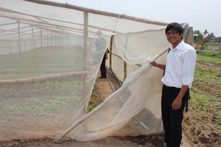 In a vegetable field, Thort holds open the net door of a net house, with someone standing inside among the vegetable rows