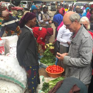Man with smartphone in crowded market, with woman selling fresh produce and bags of dried goods in Tanzania