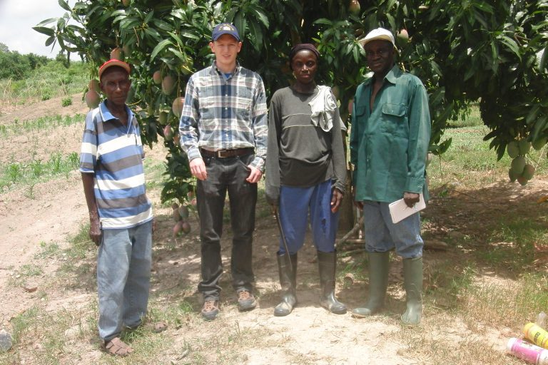 student and farmers in front of mango tree