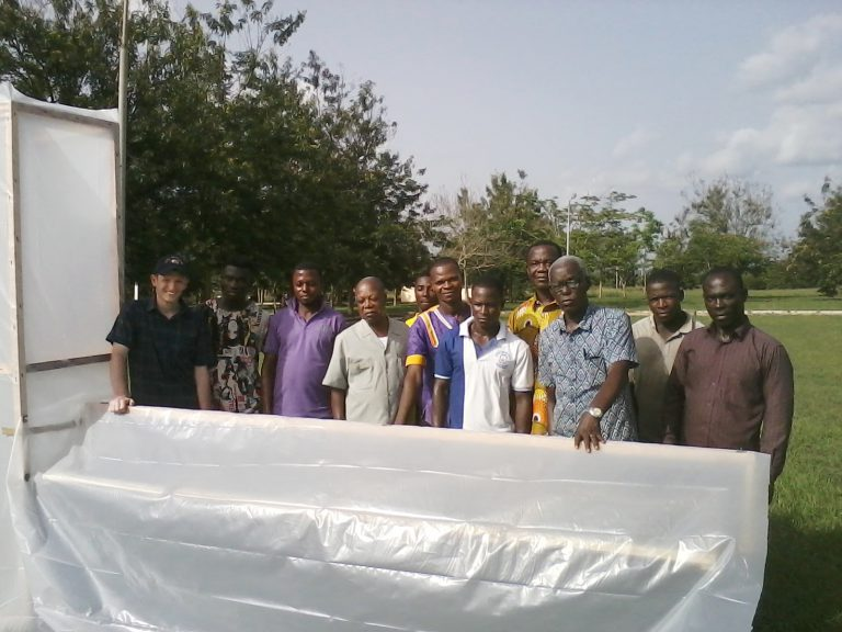 researchers with large solar dryer covered in clear plastic