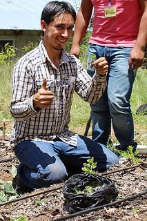 young man kneeling, smiles with a tiny seedling and a thumbs-up
