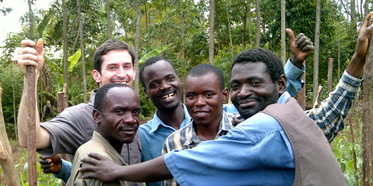 group of agricultural researchers, smiling in a field