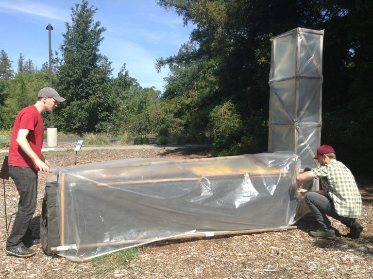 two men adjust plastic cover over chimney solar dryer outdoors