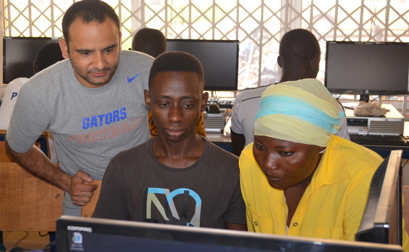 student in Florida shirt works with two students from Ghana at a computer screen