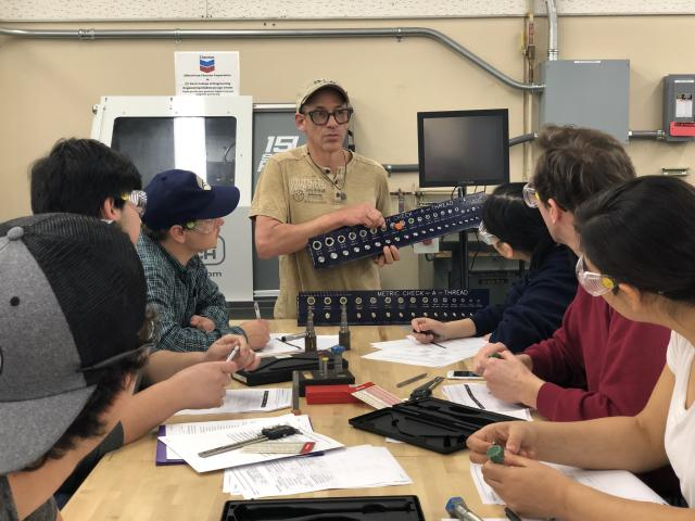 Teacher with students in D-Lab course