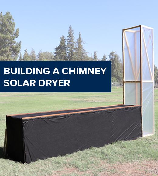 """Building a chimney solar dryer"" text on image of a chimney solar dryer in a field"