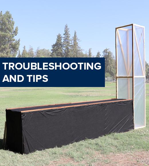 """Troubleshooting and tips"" on a photo of the chimney solar dryer in a sunny field"