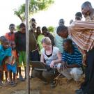 Group gathers around Darcy Boellstorff as she plugs her computer into a GIS system near Mzimba.
