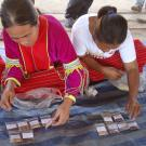 Women seated on a mat sort through labeled packets of seeds