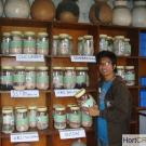Young man holds jar of seeds and drying beads in vegetable seed repository in Nepal.