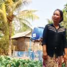 Woman farmer in Cambodia in vegetable farm blog with mulch and drip irrigation tank.