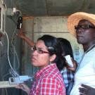 Women scientists discuss CoolBot, air conditioner, and cold storage insulation at UC Davis student farm.
