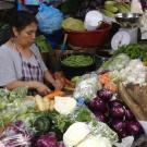 Woman chopping and weighing vegetables in a market in Guatemala