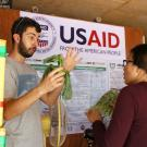 Man gestures with wilted leafy green vegetable to woman listening, with USAID logo in background of packing shed in Cambodia.