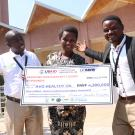 Niyidukunda Mugeni Euphrosine of Avo Healthy Oil Company grins and holds a giant check showing her award money from the competition, next to two other competitors.