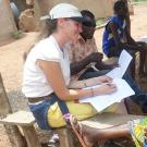 Smiling researcher takes notes while farmer speaks, seated in shade